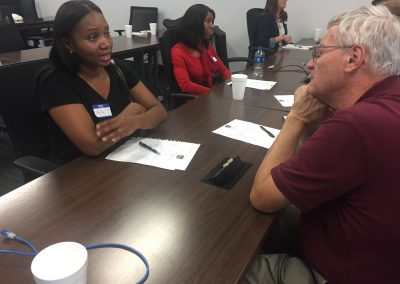 A mentor and mentee discuss shared interested while sitting at a table